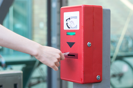Validate a ticket at a red ticket validation machine for the underground from the side