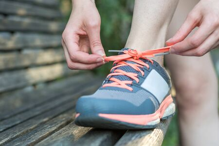 Do up the shoelaces on a park bench close up
