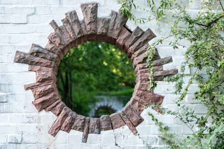 A round hole in a brick wall in a park looks like a portal to another dimension Stock Photo