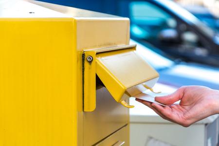 ドイツ イエローのメールボックスに手紙を投げる 写真素材