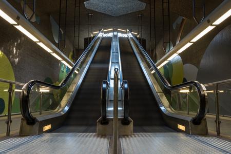 Twee bewegende ondergrondse roltrap in de metro vanaf de voorkant Redactioneel
