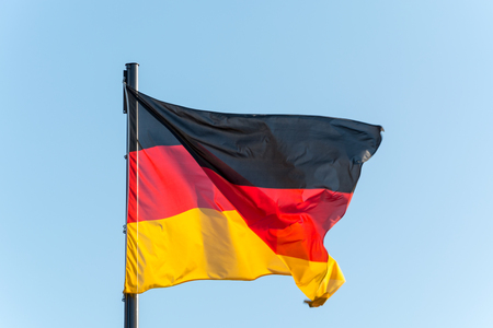 The German flag on a pole with blue sky isolated