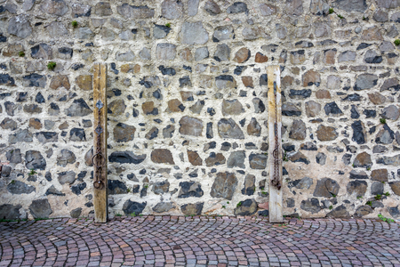 Two medieval prison chains for prisoners in front of stone wall