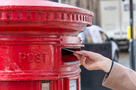 Throwing a letter in a red British post box from the side Zdjęcie Seryjne - 87560500