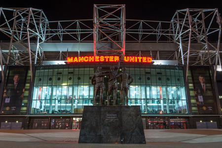MANCHESTER, ENGLAND - September 29, 2017: The stadium Old Trafford and the statue United Trinity in the night in Manchester Editorial