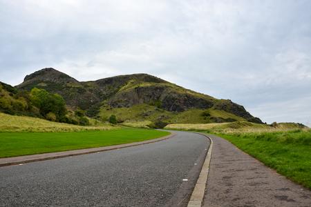 city park skyline: A street through Hollyrood park and Arthurs Seat near Edinburgh, Scotland Stock Photo