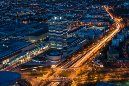 MUNICH, GERMANY - November 3, 2017: The lit BMW headquarters with light trails from traffic during blue hour from above