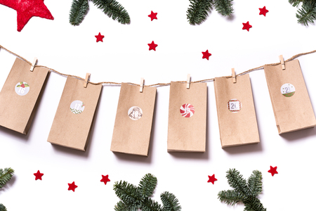 Handmade tinkered advent calendar with paper bags and stickers with fir branches and red stars on a white background