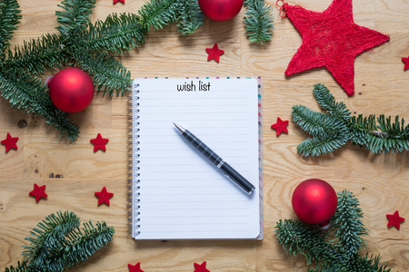 stock photo wish list for christmas on a notepad with christmas decorations and fir branches on a wooden table from above