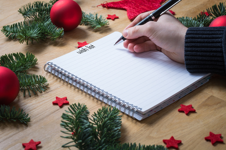 stock photo writing a wish list for christmas on a notepad with christmas decorations and fir branches on a wooden table seen from the side - Christmas Decorations List