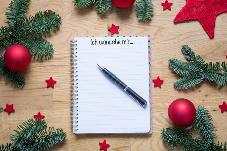 Christmas wish list with title I would like in German on a notepad with Christmas decorations and fir branches on a wooden table from above