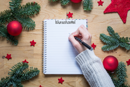 stock photo writing a wish list for christmas in german on a notepad with christmas decorations and fir branches on a wooden table from above