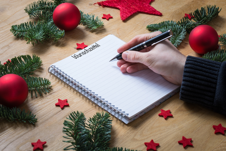stock photo writing a wish list for christmas in german on a notepad with christmas decorations and fir branches on a wooden table seen from the side