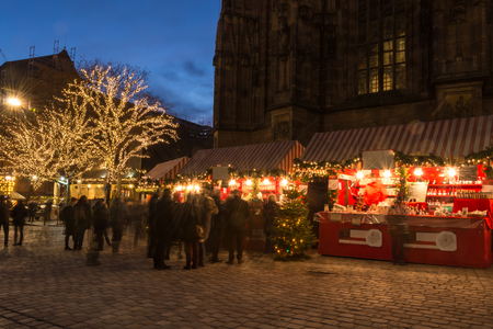 Several stands at the Christmas market in Nuremberg during blue hour with lights in the trees