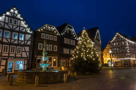 FRITZLAR, GERMANY: 25th December 2017: The marketplace of Fritzlar with fountain and Christmas tree and fairy lights during blue hour