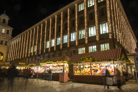 Several stands at the Christmas market in Nuremberg during blue hour in front of a building with Christmas lights