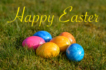 Happy Easter with several colorful Easter eggs lying on grass close up Stock Photo