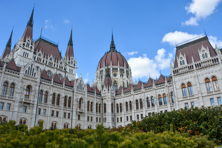 The Budapest parliament with bushes in front with blue sky