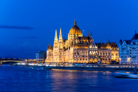 The famous Budapest parliament at the river Danube during blue hour from the side Stock Photo