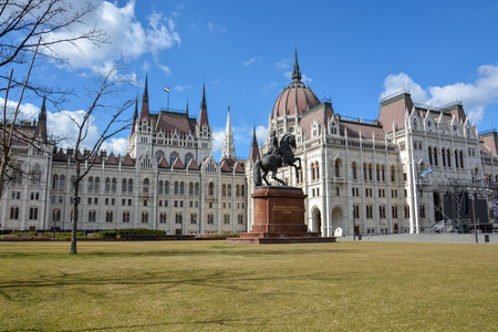 The Budapest parliament with a rider statue and blue sky Stock Photo