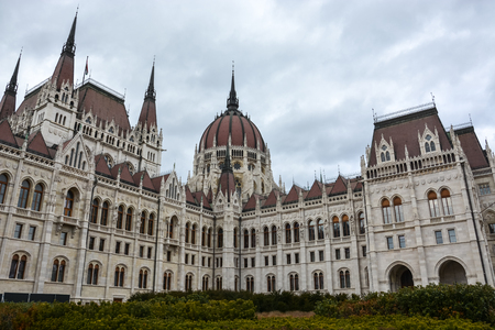 The Budapest parliament with bushes in front with cloudy sky