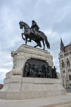 A statue of a rider in front of the Budapest parliament from the side with cloudy sky Stock Photo