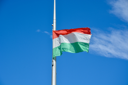 The hungarian flag on a pole waving in the wind