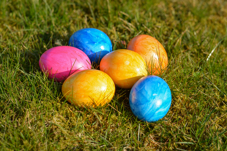 Several colorful Easter eggs lying on grass close up