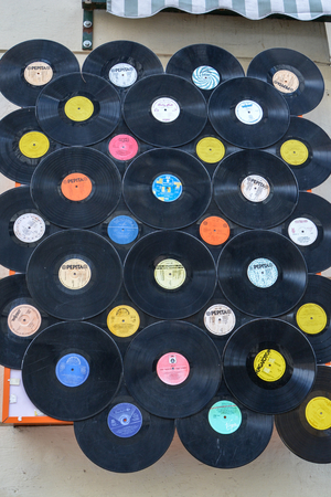 Many records hanging on a wall in the street in Budapest