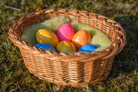 Several colorful Easter eggs in a basket on grass close up