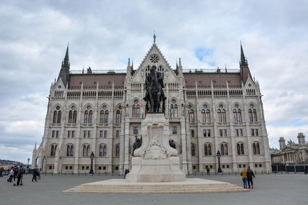 The Budapest parliament and a statue from the side with cloudy sky Editorial