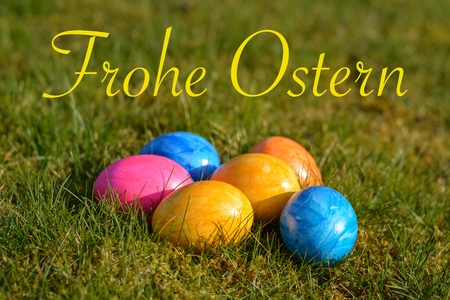 Happy Easter in German with several colorful Easter eggs lying on grass close up