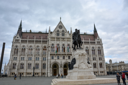 The Budapest parliament and a statue from the side with cloudy sky Stock Photo