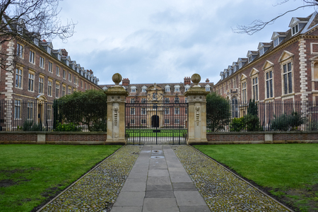 A Kings College building in Cambridge with a gate and cloudy sky