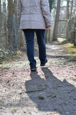 Lonely woman walking through the woods on a sunny day Stock Photo - 99373196
