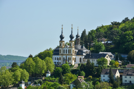 The pilgrimage church Kaeppele on a hill in Wuerzburg through the trees on a sunny day