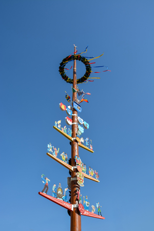 A traditional German Maibaum or may pole in Wuerzburg on a sunny day and blue sky