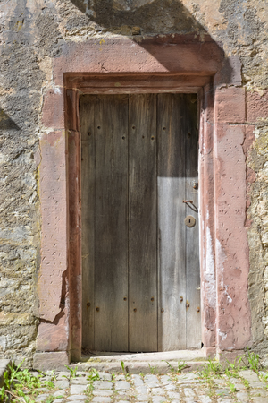 Old wooden medieval door in a stone wall on a sunny day from the front
