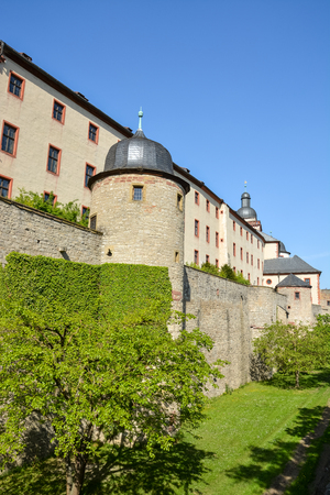 Medieval wall with climbers plants at the Marienberg castle in Wuerzburg with blue sky