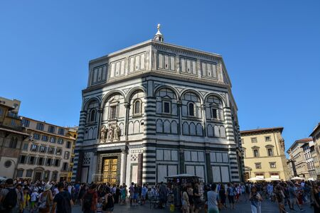 FLORENCE, ITALY - August 19, 2019: The baptistery of San Giovanni with the cathedral in Florence on a sunny day