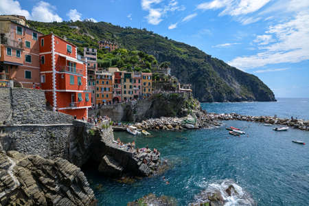 RIOMAGGIORE, ITALY - August 15, 2019: View on Riomaggiore  and the sea and cliffs at the Cinque Terre on a sunny day Editorial