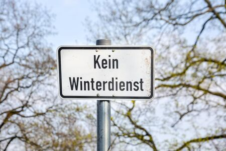 A rusty sign in German which says no winter service close up 版權商用圖片