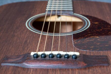 Strings of a brown wooden guitar as a close up Banco de Imagens
