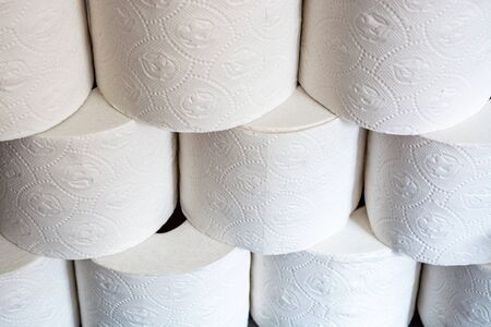 Piled up toilet paper rolls as a close up from the front at an angle