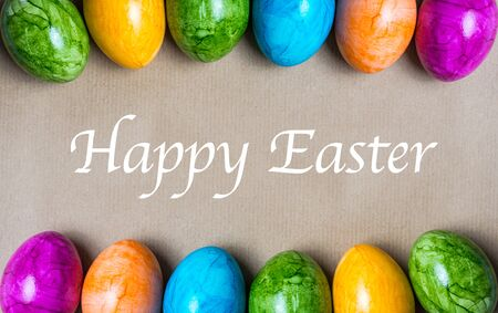 Two borders of easter eggs in different colors with text Happy Easter on a brown paper background