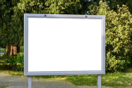 Blank ad space on a sign in a park on sunny day