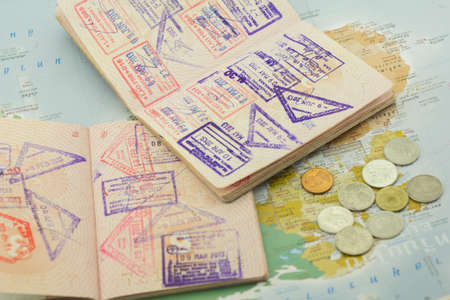 Passports with stamps and coins lie on the shown card photo