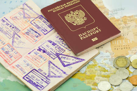 credential: Passports with stamps and coins lie on the shown card