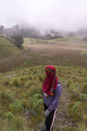 Hijab woman in semeru savana Editorial