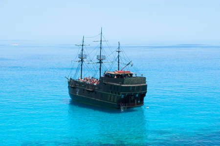 Black pirate ship on the blue sea. Back view
